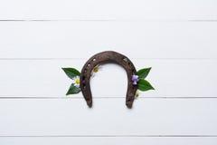 Подкова, используемая и с ржавчиной, на белизне покрасила древесину, символ для Стоковое фото RF