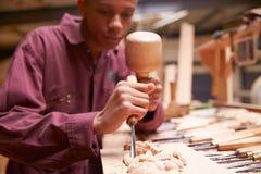 Подмастерье используя зубило для того чтобы высечь древесину в мастерской стоковое изображение