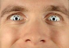 по мере того как глаза шариков восторженные дуют футбол Стоковое Изображение