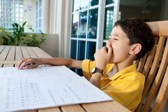 по мере того как мальчик делает его домашнюю работу зевая Стоковое фото RF