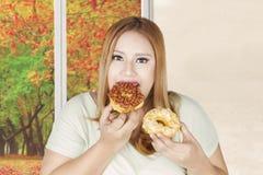 Полная женщина ест 2 donuts Стоковое Изображение RF