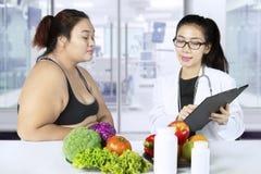 Полная женщина и доктор с результатом теста стоковая фотография