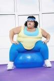 Полная женщина сидя на шарике тренировки Стоковая Фотография RF