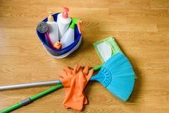 Полная коробка поставек чистки, mop, веника и перчаток на деревянном b Стоковое Изображение RF