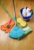 Полная коробка поставек чистки, mop, веника и перчаток на деревянном b Стоковое фото RF