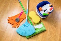 Полная коробка поставек чистки, mop, веника и перчаток на деревянном b Стоковое Фото
