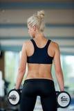 Поднимать некоторые весы и работа на ее бицепсе в спортзале Стоковое Изображение RF