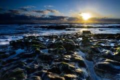 Поднимая рассвет идеи; мытье волн на скалистом береге Стоковое фото RF