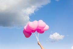 Поднимите сердце к концепции рая с рукой и воздушными шарами Стоковая Фотография