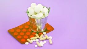 Полное ведро круглых таблеток и красной упаковки пилюлек на l Стоковая Фотография