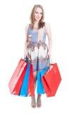 Полное тело усмехаясь молодой женщины с хозяйственными сумками Стоковые Фото
