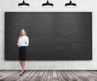 Полнометражная дама в официально одеждах Белая рубашка и черная юбка Черная доска на стене, деревянном поле и ce 3 стоковое изображение