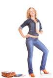 Полнометражная девушка студента в голубых джинсах кладет книги в мешки Стоковое Изображение