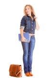 Полнометражная девушка студента в голубых джинсах кладет книги в мешки Стоковое фото RF