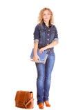 Полнометражная девушка студента в голубых джинсах кладет книги в мешки Стоковые Фото