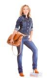 Полнометражная девушка студента в голубых джинсах кладет книги в мешки Стоковое Изображение RF