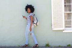 Полнометражная современная африканская женщина идя снаружи с мобильным телефоном Стоковые Изображения