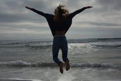 Полнометражное вид сзади женщины скача на пляж Стоковая Фотография RF