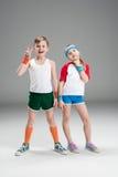 Полнометражный взгляд милого усмехаясь мальчика и девушки в sportswear стоя совместно и показывать изолированном на сером цвете Стоковые Изображения