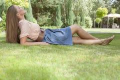 Полнометражный взгляд со стороны расслабленной молодой женщины лежа на траве в парке Стоковые Фотографии RF