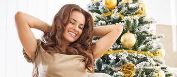 Полнометражный портрет женщины сидя около рождественской елки Стоковые Изображения RF