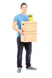 Полнометражный портрет коробок нося удаления парня Стоковые Изображения RF