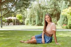 Полнометражный портрет красивой молодой женщины ослабляя в парке Стоковое Фото