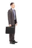 Полнометражный портрет молодого бизнесмена с стойкой портфеля Стоковая Фотография