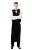 Полнометражный портрет молодого красивого кельнера стоя с cros Стоковая Фотография RF
