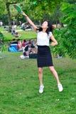 Полнометражный портрет молодой женщины играя бадминтон в Vondelpark, Амстердам Стоковое фото RF