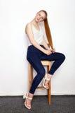Полнометражный портрет молодой красивой женщины модели beginner redhead в голубых джинсах белой футболки практикуя представлять п Стоковое Изображение