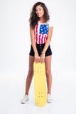 Полнометражный портрет предназначенной для подростков девушки держа скейтборд Стоковые Изображения RF