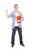 Полнометражный портрет студента при книги давая большой палец руки вверх Стоковое Изображение RF