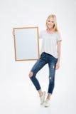 Полнометражный портрет счастливой женщины держа пустую доску Стоковые Изображения