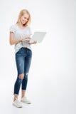 Полнометражный портрет счастливой женщины используя портативный компьютер Стоковое Изображение RF