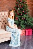 Полнометражный портрет счастливой молодой женщины сидя около рождественской елки Стоковые Изображения RF