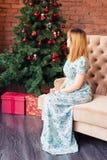 Полнометражный портрет счастливой молодой женщины сидя около рождественской елки Стоковые Фото