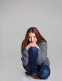Полнометражный портрет счастливых задумчивых усаживания и думать женщины Стоковая Фотография