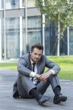 Полнометражный портрет усиленного бизнесмена сидя на пути вне офиса Стоковые Изображения RF