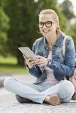 Полнометражный портрет усмехаясь молодого женского студента колледжа используя ПК таблетки в парке Стоковое Фото