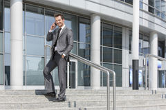 Полнометражный портрет усмехаясь сотового телефона бизнесмена отвечая пока стоящ на шагах вне офиса Стоковая Фотография