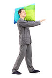 Полнометражный портрет человека ходить и держа подушка Стоковые Фото
