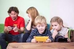Полностью усаживание семьи fascinated телефоны и smartphones стоковое фото rf
