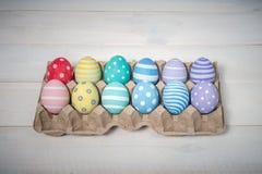 Поднос с 12 красочными handmade пасхальными яйцами лежит на белой деревянной предпосылке, в центре Стоковая Фотография