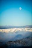 Полнолуние над снежными горами Стоковая Фотография