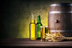 Полные бутылки пива и стекла с бочонком Стоковое Изображение