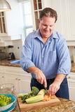 Полный человек подготавливая овощи в кухне стоковое изображение