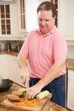 Полный человек подготавливая овощи в кухне стоковое изображение rf