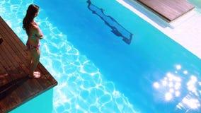 Подныривание брюнет в ясный голубой бассейн акции видеоматериалы