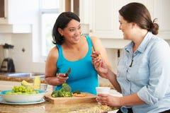 2 полных женщины на диете подготавливая овощи в кухне Стоковое Изображение RF